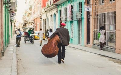 Man carrying base instrument in Cuba
